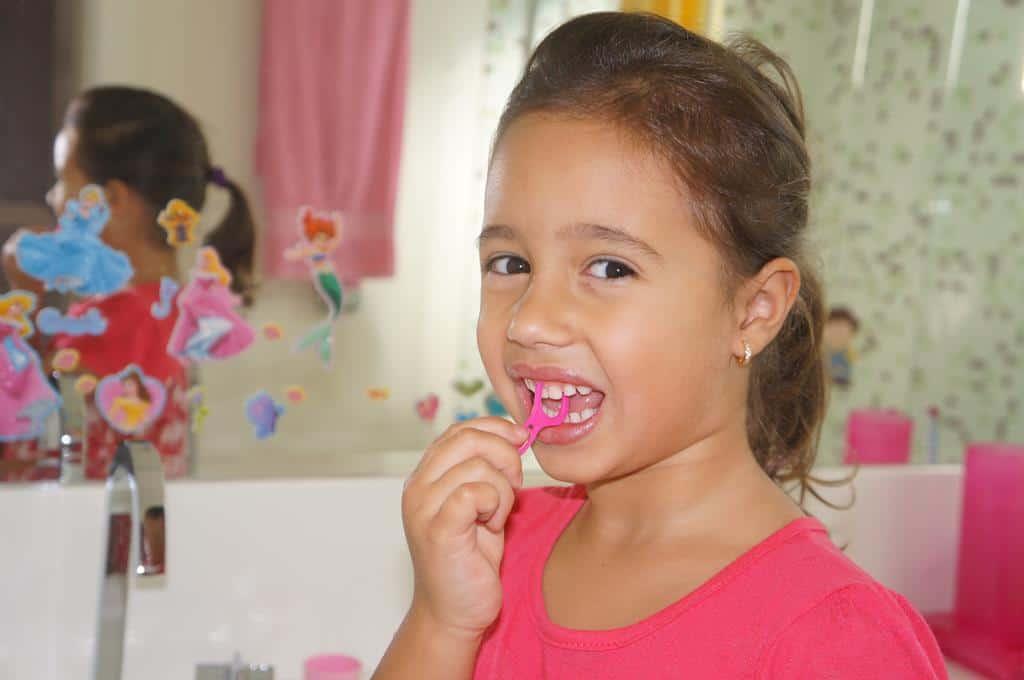 criança passando fio dental